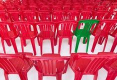 Chaise verte parmi le rouge ceux Photos libres de droits