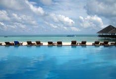 Chaises étonnantes de piscine et de plate-forme devant la mer Images stock