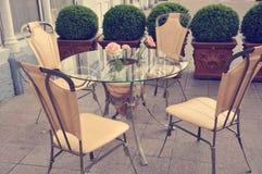 Chaises Arround le Tableau en verre avec des fleurs Images stock