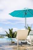 Chaises avec le parasol bleu le jour ensoleillé Photos stock