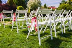 Chaises blanches avec des rubans de couleurs de rose et de pêche Photographie stock libre de droits