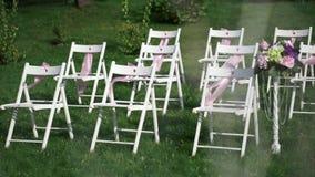 Chaises blanches avec les arcs roses ondulant dans le vent Décor de mariage pour l'enregistrement en plein air banque de vidéos