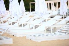 Chaises blanches de piscine sur la plage de sable Images libres de droits