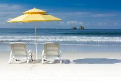 2 chaises blanches et parapluie jaune sur la plage tropicale Image stock