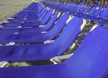 Chaises bleues sur la plage dans une rangée image stock