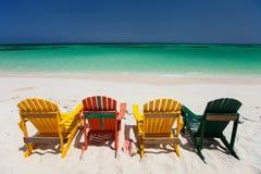 Chaises colorées sur la plage des Caraïbes Photographie stock libre de droits