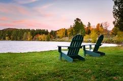 Chaises d'Adirondack près du rivage d'un lac au crépuscule Photos libres de droits