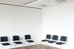 Chaises dans des murs blancs de salle d'attente, vue faisante le coin photos stock