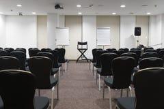 Chaises dans une rangée dans la salle de conférence Photographie stock libre de droits