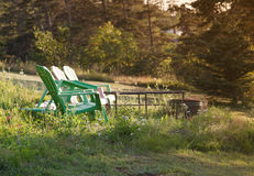 Chaises de jardin vertes par un puits du feu photographie stock