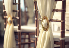 Chaises de mariage dans la rangée décorées du cercle de couleur d'or élégant Photographie stock libre de droits