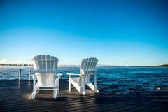 Chaises de Muskoka sur un dock avec l'augmentation et la brume du soleil Images stock
