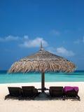 Chaises de parapluie et de soleil Images stock