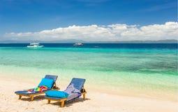 Chaises de plage, eau claire et belle vue sur l'île tropicale, Photos libres de droits