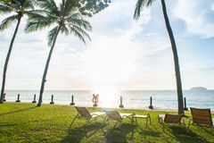chaises de plage sous le palmier regardant le coucher du soleil Photos stock