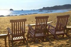 Chaises de plage sur la plage de sable devant des vagues Photographie stock