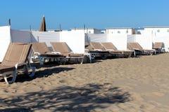 Chaises de plate-forme beiges de plage avec les écrans blancs Photo stock