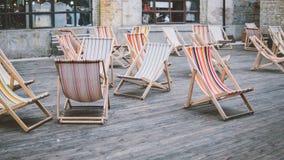 Chaises de plate-forme colorées dehors Séjour à l'air frais Confort et canapés du soleil dans la ville Orientation peu profonde Photographie stock libre de droits