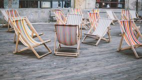 Chaises de plate-forme colorées dehors Séjour à l'air frais Confort et canapés du soleil dans la ville Orientation peu profonde Photographie stock
