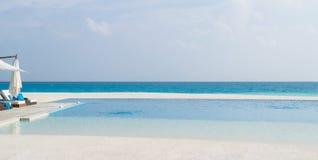 Chaises de plate-forme et piscine d'infini au-dessus de stupéfier la lagune tropicale en Maldives photos libres de droits