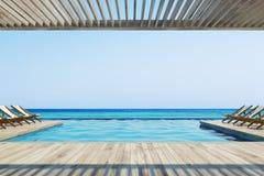 Chaises de plate-forme près d'une piscine Images stock