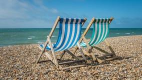 Chaises de plate-forme sur un Pebble Beach photo stock