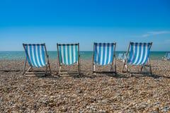 4 chaises de plate-forme sur un Pebble Beach Photographie stock