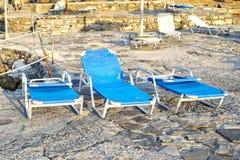 Chaises de plate-forme sur une plage sablonneuse Image stock