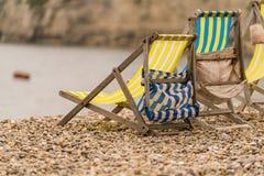 Chaises de plate-forme vides sur un Pebble Beach Photographie stock