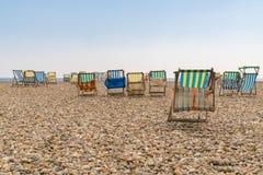 Chaises de plate-forme vides sur un Pebble Beach Images libres de droits