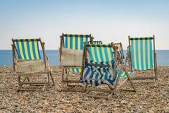 Chaises de plate-forme vides sur un Pebble Beach Image libre de droits