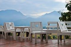 Chaises en bois blanches d'amour sur le balcon en flanc de coteau de village de Pai Photographie stock