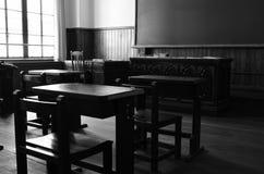 Chaises en bois dans une vieille salle de classe Photos stock