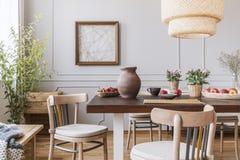 Chaises en bois de cru dans le salon avec la longue table avec des fraises, des pommes, le vase et des fleurs là-dessus, vraie ph photos stock