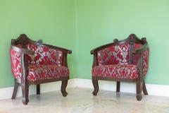 Chaises en cuir rouges dans le coin avec les murs verts comme fond photographie stock