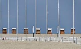 Chaises et mâts de drapeau de plage en osier couverts Photographie stock libre de droits