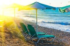 Chaises et parapluie de plage sur le rivage d'une plage de galets Grèce Rhodes avec du temps de crépuscule de fusée du soleil Images libres de droits