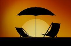 Chaises et parapluie sur un coucher du soleil de fond Photographie stock
