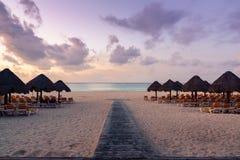 Chaises et parapluie sur une plage au lever de soleil - hutte de Palapa Images libres de droits