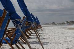 Chaises et parapluies de plage à la plage obscurcie Photos stock