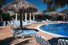 Chaises et piscine sur une station de vacances du Cuba Images libres de droits