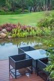 Chaises et table classiques de rotin sur le balcon en bois près du petit beau lac dans un jardin de plante verte photos libres de droits