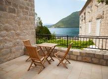 Chaises et table en bois sur la terrasse de bord de la mer Photos stock
