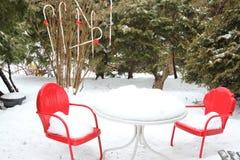 Chaises et table rouges dans la neige Images stock