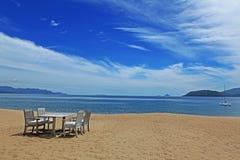 Chaises et table sur la plage Photographie stock