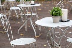 Chaises et tables blanches en métal en parc Photos stock