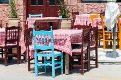 Chaises et tables en bois à la taverne grecque traditionnelle Images libres de droits