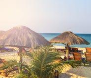 Chaises longues de plage sous la tente sur la plage Photo libre de droits