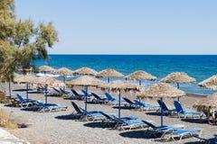 Chaises longues de plage sur la plage noire de sable photographie stock
