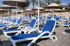 Chaises longues et parapluies vides avec un toit couvert de chaume sur la plage Image stock